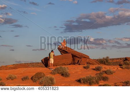Horseshoe Bend, Arizona / Usa - October 25, 2014:  A Man Takes A Picture Of A Woman Sitting On An Or