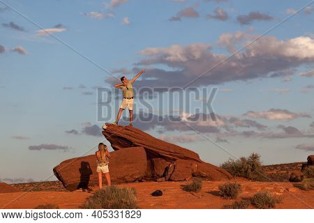 Horseshoe Bend, Arizona / Usa - October 25, 2014:  A Woman Takes A Picture Of A Man Posing On An Ora