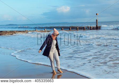 Woman In Warm Clothes And Sunglasses Playing With Waves At Seaside, Enjoying The Moment During A Wal