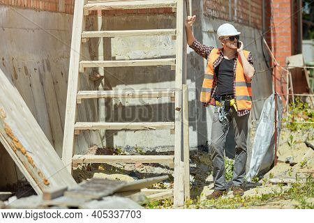A Construction Engineer In A Checked Shirt, Orange Vest, And White Hard Hat On A Yellow Construction