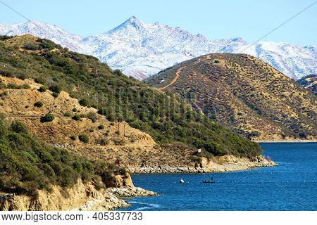 Chaparral Covered Hills With Snow Capped Mountains Beyond Surrounding Silverwood Lake, Ca Taken In T