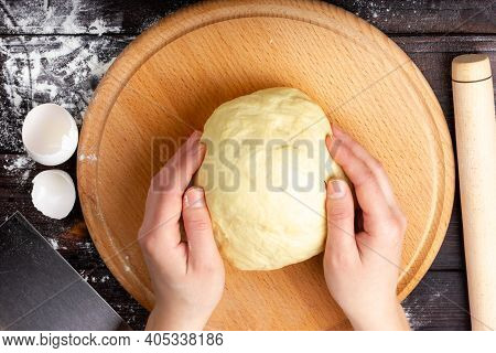 The Process Of Making Bread Dough. Female Hands Hold The Dough. The Dough Is On The Table. Flat Lay.