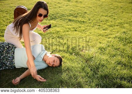 Woman Checking Pulse Of Unconscious Person With Heart Attack In Park