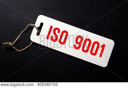 Notebook With Text Inside Iso 9001 On Table With Coffee, Mobile Phone And Glasses.
