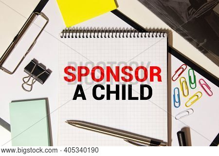 Sponsor A Child Text Written On A Notebook With Pencils