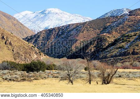 Rural Grasslands Surrounded By Arid Hills And Snow Capped Mountains Beyond Taken At Barren Badlands