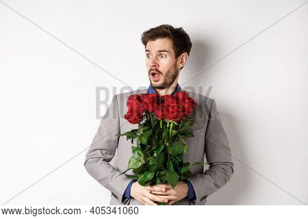 Handsome Young Man In Suit Holding Red Roses, Looking Left With Surprised And Startled Expression, S