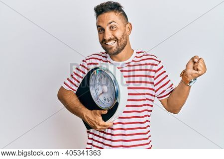 Handsome man with beard holding weight machine to balance weight loss screaming proud, celebrating victory and success very excited with raised arm