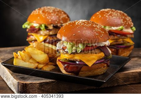 Three yummy grilled burger with double meat cutlet and fries on a wooden table, side view. Hamburger and French fries. Fast food.