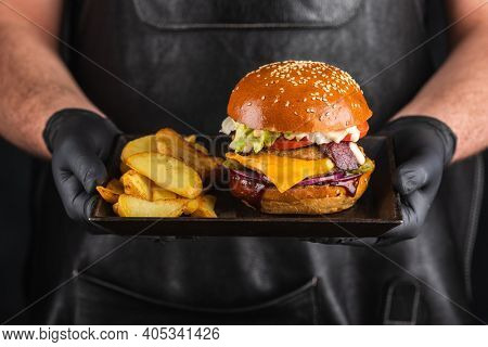 Grilled hamburger with meat cutlet and French fries in hands. Fast food concept. Homemade burger. Fried potatoes and cheeseburger.