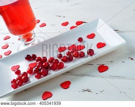 Selective Focus On Cranberries On A White Plate On A White Wooden Background. In The Background, A F