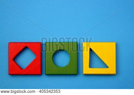 Colorful Children's Wooden Toy. Sorter Of A Cube Shape On A Blue Background. Children's Brain Traini