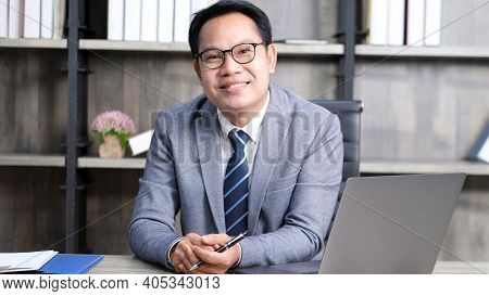 Portrait Of Senior Asian Businessman Smiling And Looking At Camera While Sitting At Office, Executiv
