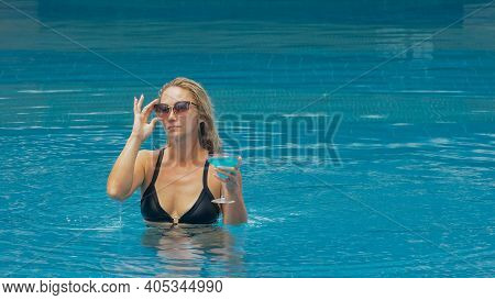 The Wide Middle Shot Pretty Woman Drinking Blue Cocktail Alcohol Liquor In Swimming Pool At Hotel. P