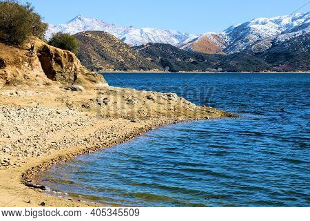 Sandy Beach Cove On Silverwood Lake, Ca Which Is Surrounded By Rugged Mountains Covered With Snow Ta