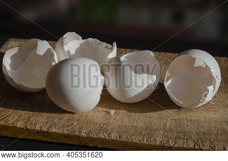 White Shells Of Chicken Eggs Close-up. Broken Shell Of Five Raw Chicken Eggs On A Wooden Cutting Boa