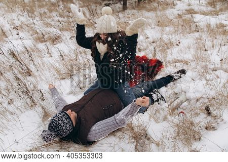 The Woman Sits On The Man. Couple Playing Snowballs In A Winter Snowy Field. The Man Lies In The Sno