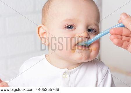 Mother Feeding Baby With Blue Baby Spoon. First Baby Fruit Puree. Close Up Photo Of Caucasian Baby B