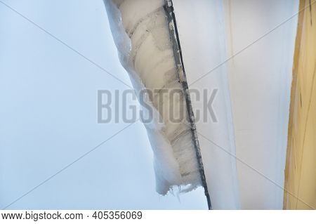 Ice And Snow Covers Roof Building, Dangerous Ice Dams Hanging From Roof.  Danger And Safety Concept