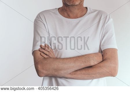 A Middle-aged Man With Stubble In A White Blank T-shirt And Hands Folded Across His Chest Against A
