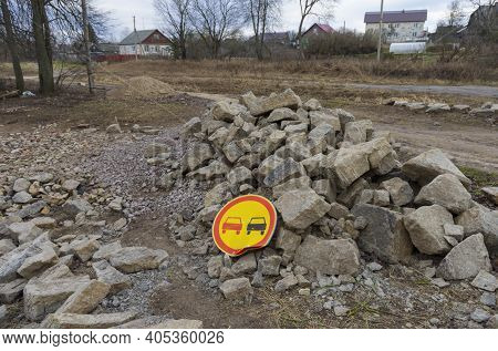 Bent Widespread Road Sign 'no Overtaking' On A Large Pile Of Rocks