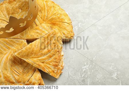 Traditional Galette Des Rois With Paper Crown On Grey Marble Table, Above View. Space For Text