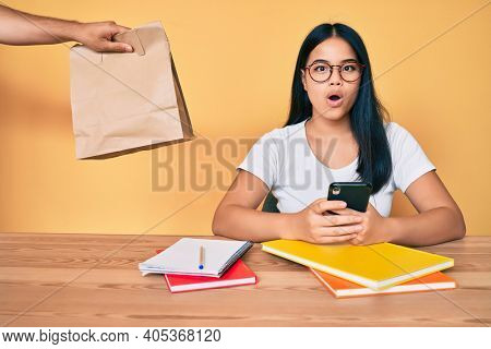 Young beautiful asian girl sitting on the table stuying getting take away food scared and amazed with open mouth for surprise, disbelief face