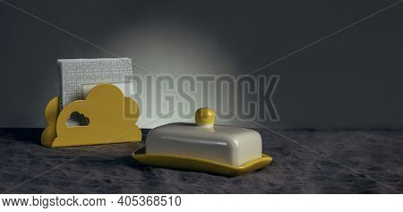 Still Life Of An Oilcan And A Yellow Napkin Holder With White Napkins On A Tablecloth Made Of Gray N