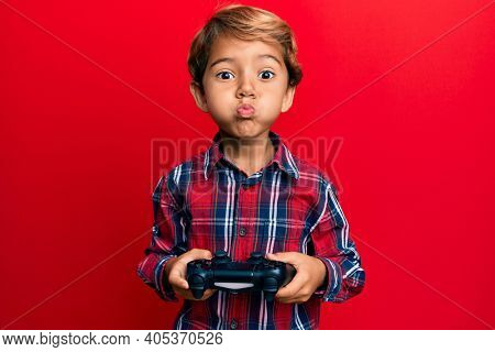 Adorable latin kid playing video game holding controller puffing cheeks with funny face. mouth inflated with air, catching air.