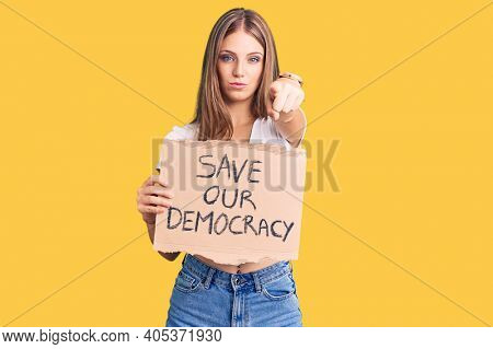 Young beautiful blonde woman holding save our democracy protest banner pointing with finger to the camera and to you, confident gesture looking serious