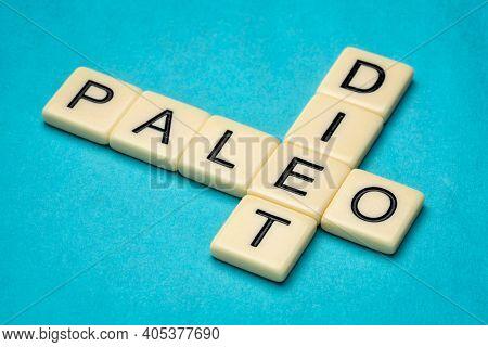 paleo diet  crossword in ivory letter tiles against textured handmade paper, healthy eating concept