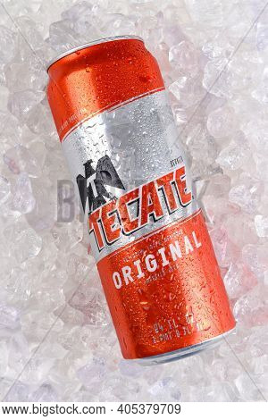 IRVINE, CALIFORNIA - MARCH 21, 2018: A Tecate Original Cerveza 24 ounce can on ice. Cuauhtemoc Moctezuma Brewery is a major brewer based in Monterrey, Nuevo Leon, Mexico, founded in 1890.