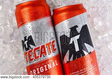 IRVINE, CALIFORNIA - MARCH 21, 2018: Two Tecate Original Cerveza cans on ice closeup. Cuauhtemoc Moctezuma Brewery is a major brewer based in Monterrey, Nuevo Leon, Mexico, founded in 1890.