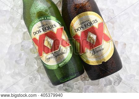IRVINE, CA - JUNE 14, 2017: Dos Equis Blanca and Especial on ice. Two bottles the beer from Cuauhtemoc-Moctezuma Brewery in Monterrey, Mexico a subsidiary of Heineken International.