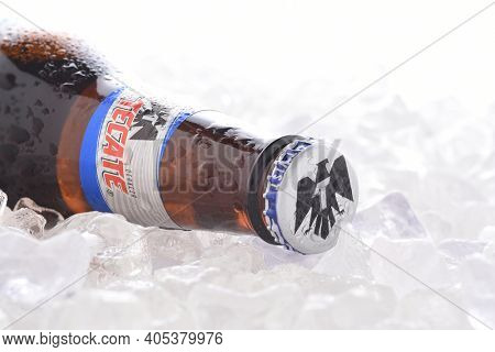 IRVINE, CA - JUNE 14, 2017: Tecate Light bottle on Ice.  A bottle of Tecate Light, a popular pale lager named after the city of Tecate, Baja California, where it was first produced in 1943.
