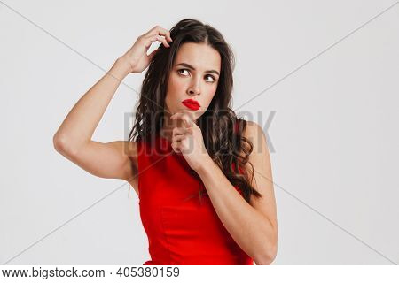 Perplexed beautiful girl wearing red dress thinking and looking aside isolated over white background