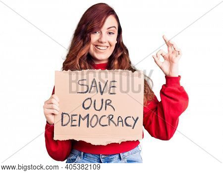 Young beautiful woman holding save our democracy protest banner doing ok sign with fingers, smiling friendly gesturing excellent symbol