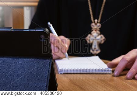 . Conference Of Orthodox Priests. Work Online. An Orthodox Preacher With A Cross On His Chest Sits O