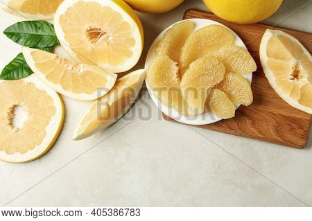 Ripe Pomelo And Plate With Pomelo Slices On White Textured Background
