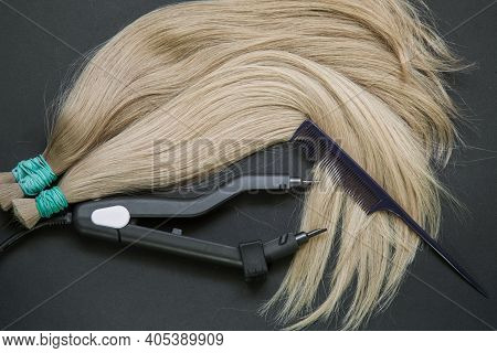 A Large Strand Of Hair With A Thin Comb-scissors Device For Encapsulating . High Quality Photo