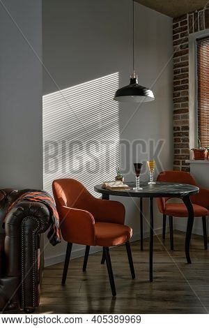 Stylish Loft-style Dining Area With Black Wood Table And Red Armchairs. Sunshine Morning Light From