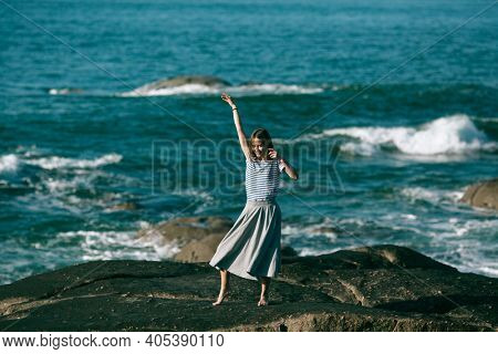 The dancer woman is engaged in choreography on the rocky Alantic.