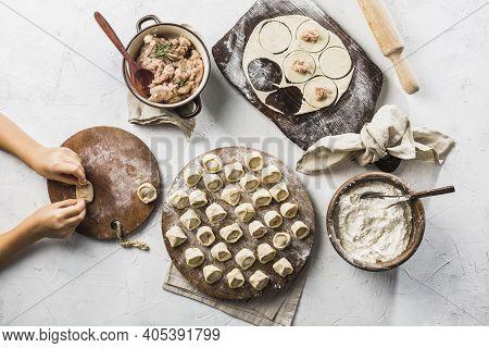 The Process Of Making Dumplings - Children's Hands Make Dumplings. A Lot Of Ready To Cook Pork Dumpl