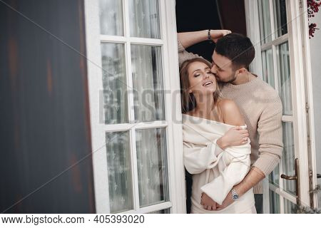 The Guy And The Girl Hug, Spending Time Together At The Open Door Of The Veranda, Looking At The Win
