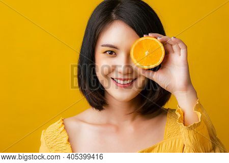 Beautiful Portrait Young Asian Woman With Orange Fruit In Studio Yellow Background. Isolated Asian G