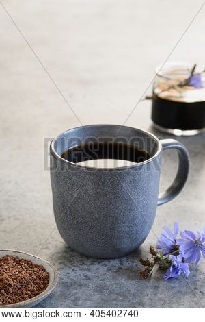 Chicory Beverage As Coffee Substitute In Grey Cup And Fresh Flowers. Vertical Format.