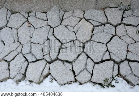Snow Covered Concrete Tiles. The Pattern Is Irregularly Cracked As After An Earthquake. Repeating Pa