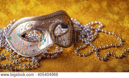 Festive, Colorful Mardi Gras Or Carnivale Mask And Beads On Golden Background. Venetian Masks. Party