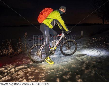 Mountain Biker Ride Alone In Snowy Winter Night. Tall Biker Wear Green Black Thermal Suit For Winter