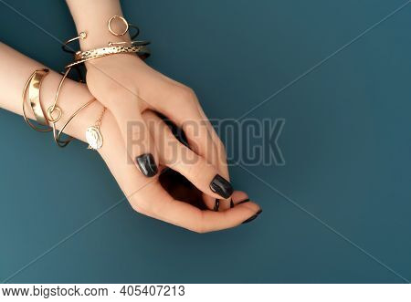 Female Hands With Trendy Dark Nail Design With Gold Bracelets On Aqua Background. Luxury Concept. Fe